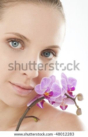 Close-up of a beauy with an orchid next to her face