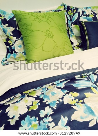 Close-up of a bed. Blue and green bed linen with floral design. - stock photo