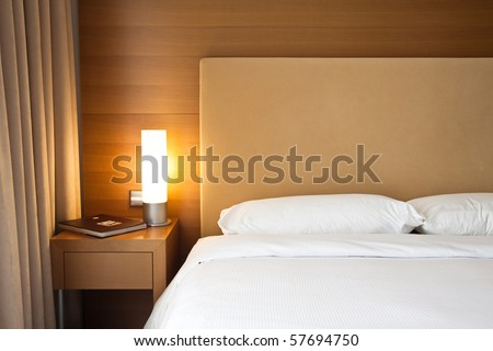 Close up of a bed with white sheets and a cozy lamp - stock photo
