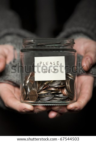 Close up of a Beggars hands and jar of coins