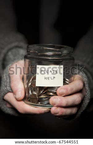 Close up of a Beggars hands and jar of coins - stock photo