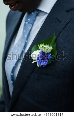 Close up of a best men with a a white and blue boutonniere  - stock photo