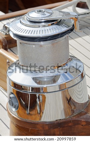 Close-up of a big cromed winch on a wooden sailboat
