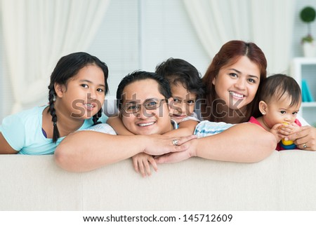 Close-up of a big family smiling and looking at camera - stock photo