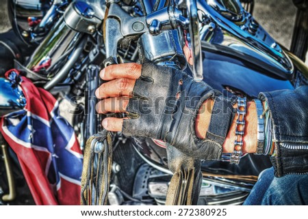 close up of a biker hand with glove on the handlebar