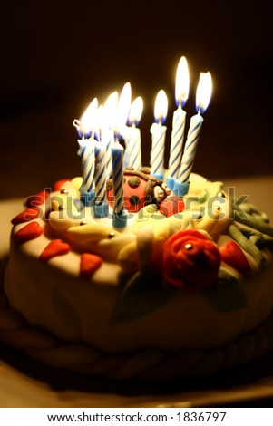 Close up of a birthday cake all lit up in the dark - stock photo