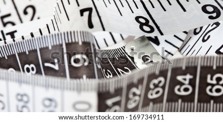 Close-up of a black and white measuring tape, symbol of tailoring, weight loss and diets