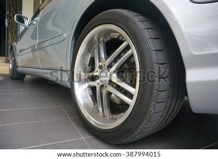 Close up of a black car tyre park at home. Sliver car with tyre                                - stock photo