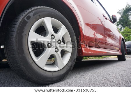 Close up of a black car tyre park on the road.Red car tyre in black. - stock photo