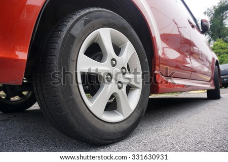 Close up of a black car tyre park on the road. Red car with tyre - stock photo