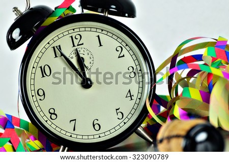 close up of  a black retro alarm clock, around midnight, with paper streamers and cork from a bottle of sparkling wine,  horizontal, slanted / New Year´s Eve - stock photo