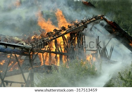 Close up of a blazing fire burns through the roof rafters of an old farm home on a mountain resort
