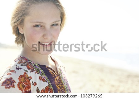 Close up of a blond girl standing on a beach shore, smiling at the camera.