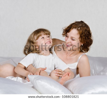 Close-up of a blond little girl and her mother lying on a bed