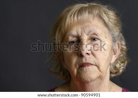 Close-up of a blond senior woman deep in her thoughts over dark background, great details of the aging skin. - stock photo