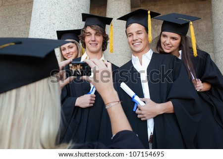 Close-up of a blonde graduate taking a picture of her friend in front of the university - stock photo