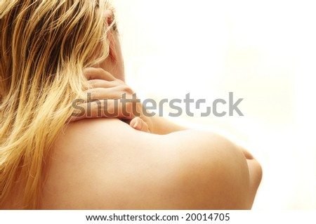 close up of a blonde woman massaging her neck