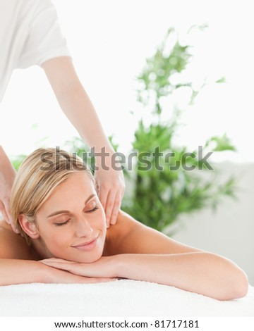 Close up of a blonde woman relaxing on a lounger enjoys a massage in a wellness center - stock photo