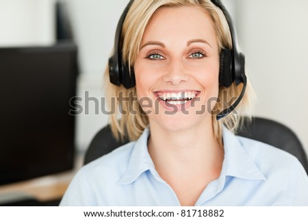 Close up of a blonde woman wearing headset looking into camera in her office