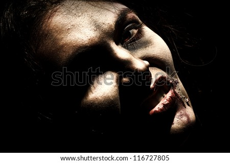 Close-up of a bloodthirsty zombi over black background. - stock photo
