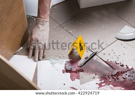 Close up of a bloody splash, hand in a white glove - stock photo