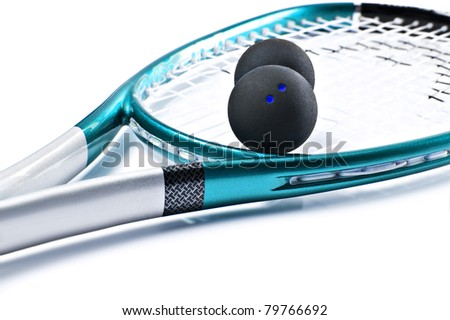 Close up of a blue and silver squash racket and ball on a white background with space for text - focus on the dots of the ball - stock photo