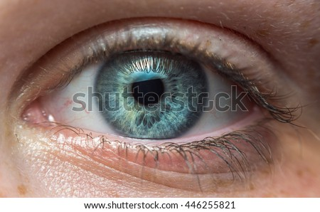 Close-up of a blue eye of a young girl staring straight into the camera - stock photo