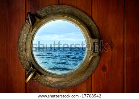Close-up of a boat closed porthole with ocean view - stock photo