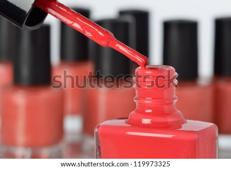 Close-up of a bottle of red nail polish with other bottles in background - stock photo