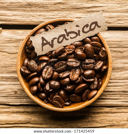 Close up of a bowl full of Arabica coffee beans over an old wooden table - stock photo