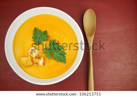 Close up of a bowl of carrot soup on red surface.