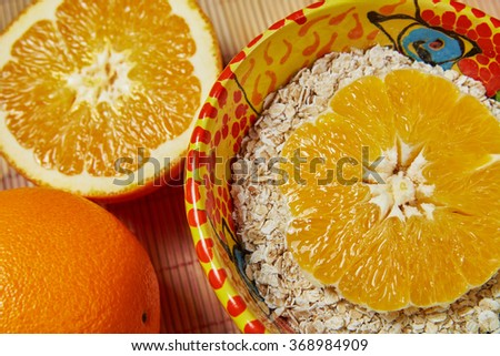 Close up of a bowl of muesli with a sliced fresh orange - stock photo