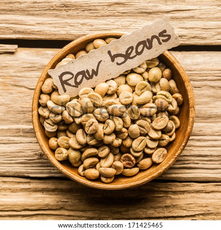 Close up of a bowl of raw coffee beans over an old wooden table - stock photo
