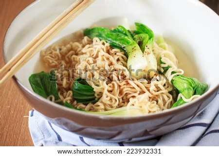Close up of a bowl with noodle soup. Chopsticks are beside the bowl.