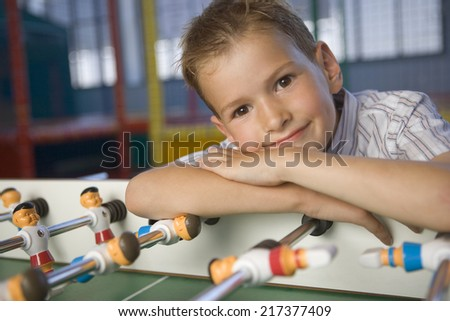 Close-up of a boy leaning on a Football table - stock photo
