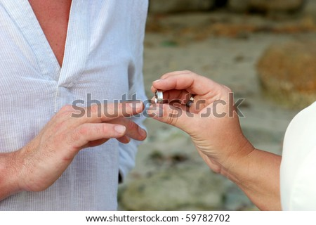 Close-up of a bride and groom exchanging wedding rings. - stock photo
