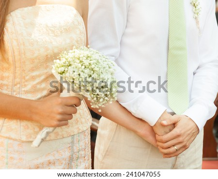 Close up of a bride and groom holding hands during wedding ceremony. - stock photo