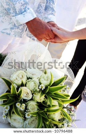 Close-up of a bride and groom holding hands with wedding bouquet in the foreground. - stock photo