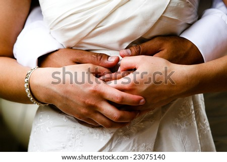 Close-up of a bride and groom in an embrace. - stock photo