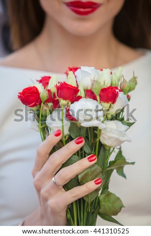 Close up of a bride holding a wedding bouquet with red and white roses.