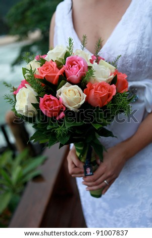 Close-up of a bride holding her wedding bouquet. - stock photo