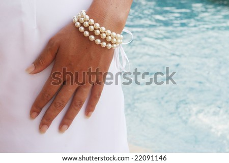 Close-up of a bride's hand with a pearl bracelet. - stock photo