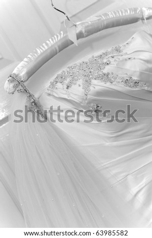Close up of a brides dress on hanger - stock photo