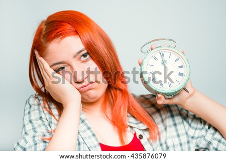 close-up of a bright red-haired girl wants to sleep with an alarm clock - stock photo