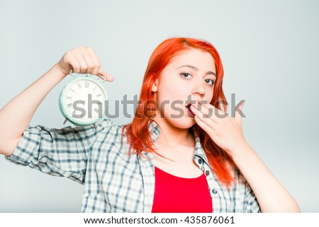 close-up of a bright red-haired girl yawns with a retro alarm clock - stock photo