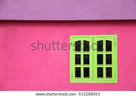 Close up of a brightly colored building with pink walls, lime green windows & purple roof, Caribbean.
