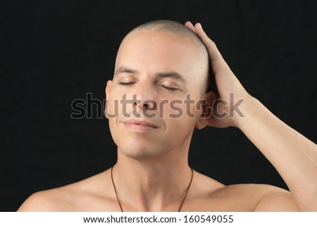 Close-up of a buddhist man feeling his newly shaved head, shirtless. - stock photo