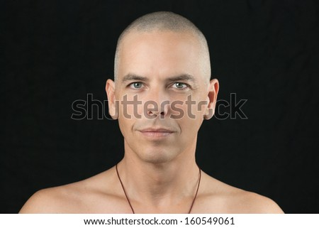 Close-up of a buddhist man looking to camera, shaved head and shirtless. - stock photo