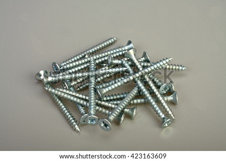 Close up of a bunch of stainless steel screws on a photographic neutral gray background. - stock photo
