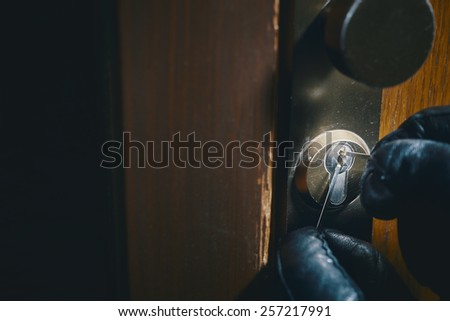 close up of a burglar with gloves picking a lock - stock photo